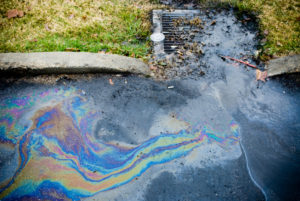 Oil runoff into a storm drain.